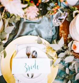 plating for a wedding complete with floral arrangements, cake, seating tags, and antique silverware