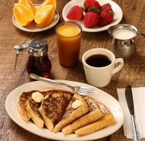 a gourmet breakfast of buttery french toast, fresh strawberries, cut orange slices, orange juice, and coffee served on a wood grain table